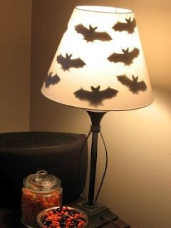 Bat shapes taped inside a lampshade create a fun Halloween look. Learn more on LightsOnline.com Blog.